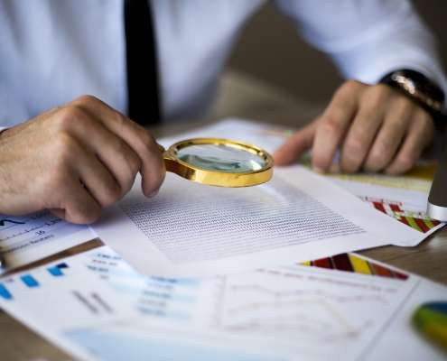 using magnifying glass to conduct background checks