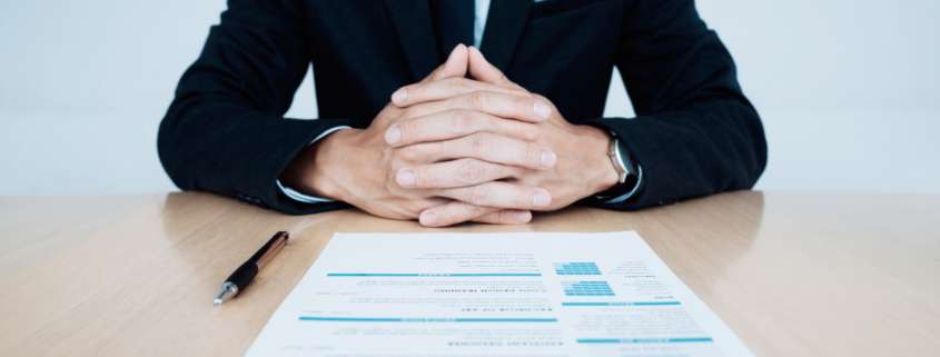 HR and resume of applicant undergoing background check and interview on table.