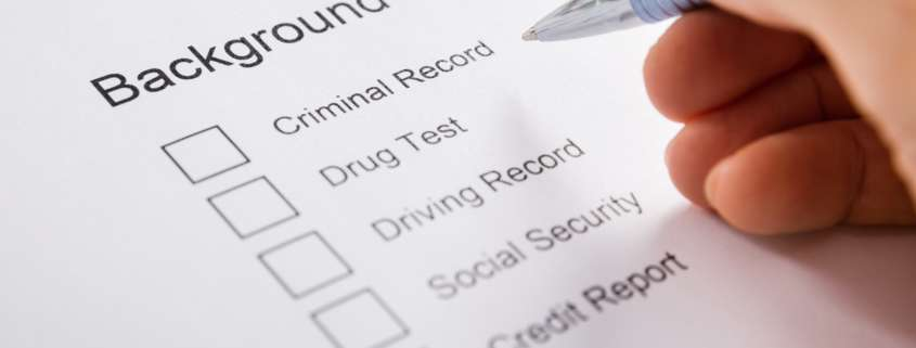 Close-up Of Person Hand Filling Background Check Provider Form