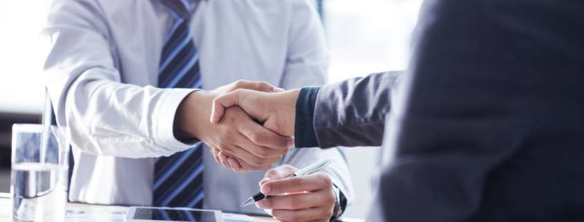 Cropped shot of two men shaking hands in background checking service