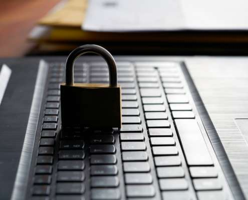 Computer keyboard and padlock as a symbol of network admin preforming principle of least privilege
