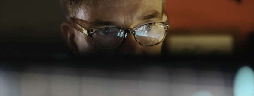 Man looking at a background check provider's national accreditation on computer