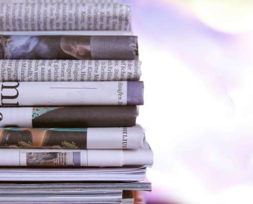 Stack of newspapers with negative headlines