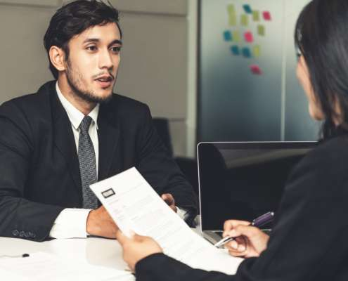 Human resource manager interviewing the male employment candidate in the office room after background checks